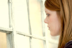 Girl and windows. Pretty young girl looking through some old broken windows Royalty Free Stock Photography