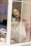 Girl on a windowsill wagging to someone. Royalty Free Stock Photography