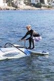 Girl windsurfer raising sail Stock Images