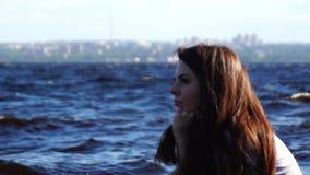 Girl on windy lake thinks stock footage