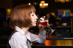 Girl with wine. Young woman drinking red wine in bar Stock Photography