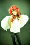 Girl with wings.. Young model wearing a red wig and angel wings.  Portrait orientation Stock Photography