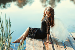 Girl with wings of an angel sitting near a river. Royalty Free Stock Photo