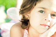 Girl with wings at the park. Beautiful girl with green eyes, wearing pink, and with wings in the park Stock Photo