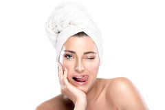 Girl Winking with Funny Expression. Spa Woman. Beautiful girl after shower winking with towel on head and funny expression sticking his tongue. Spa treatment Stock Photos