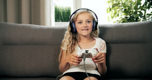 Girl winning video game. Cheerful girl dressed in casual clothing with earphones on head winning video game, sitting on cozy sofa at home, leisure activity stock footage