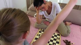 Girl wins her mother in chess stock footage