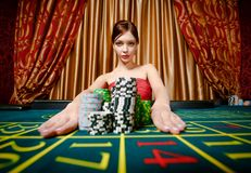 Girl wins and takes away piles of chips Royalty Free Stock Photo