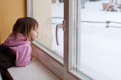 Girl and winter behind window. Little beauty girl look out of the window and breathe on the glass so that it grow misted. Winter royalty free stock image