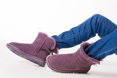 Girl in winter boots. Female Australian shoes. Girl in winter boots and jeans on a white background Stock Photos