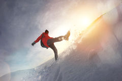 Girl in winter clothes and a backpack walking on snow hills. Snow flies from under his feet. Lens flare effect Stock Photography