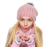 Girl in winter clothes blowing snow from hands Royalty Free Stock Photography