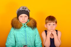 A girl in winter clothes and a boy in summer clothes are standing nearby.  stock image