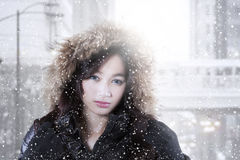Girl with winter clothes in the city. Pretty teenage girl wearing winter clothes with furry hood and snowfall in the city Stock Photo