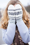 Girl in winter clothes covered her face with wool mittens Royalty Free Stock Images