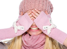 Girl in winter clothes covering eyes with hands Stock Photos