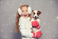 Girl in winter clothes with dog Stock Photos
