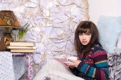Girl in winter clothes drinking tea Stock Photos