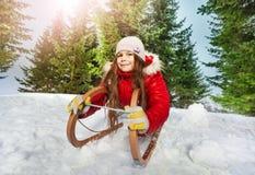Girl in winter clothes having fun on snow sledge Stock Photos