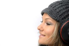 Girl with winter clothes and headphones Stock Photos