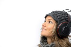 Girl with winter clothes and headphones Stock Images