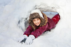 Girl in winter clothes playing at a snow hole Royalty Free Stock Photos
