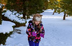 A girl in winter clothes runs to a snow hill with a playing in winter with snow stock photo