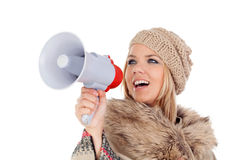 Girl with winter clothes screaming on a megaphone Royalty Free Stock Photography