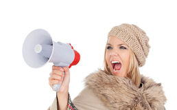 Girl with winter clothes screaming on a megaphone Royalty Free Stock Photos