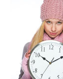 Girl in winter clothes showing clock Stock Photo