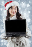 Girl in winter clothes showing laptop screen. Portrait of pretty girl wearing winter jacket and christmas hat, showing empty laptop screen stock image