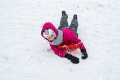 Girl in winter clothes on sled Stock Image