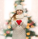 Girl in winter clothes with small red heart Stock Image