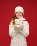 Girl in winter clothes with something on palms Royalty Free Stock Photography