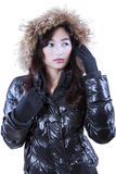 Girl with winter clothes stare copyspace in studio. Pretty young woman in warm winter jacket with fur hood, staring at the copyspace in studio stock image