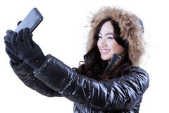 Girl in winter clothes taking self photo Royalty Free Stock Image
