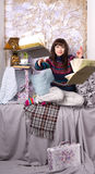 Girl in winter clothes throwing books Royalty Free Stock Image