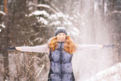 Girl in winter clothes throwing snow up in air Royalty Free Stock Photography