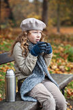 Girl in winter cloths drinking from flask cup Stock Photos