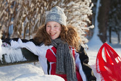 Girl in winter cloths with red sledge. Blond teenager girl sitting on a bench in a snowy park Royalty Free Stock Photos