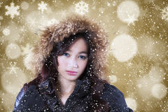 Girl with winter coat and defocused background. Portrait of attractive teenage girl wearing winter coat with furry hood and bokeh background Stock Photos