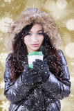 Girl with winter coat enjoy hot drink. Beautiful teenage girl wearing winter jacket with furry hood, enjoy hot drink in a cup with bokeh background Royalty Free Stock Images