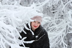 Girl in winter coat and hat in winter forest. Girl in winter coat and hat near the snow-covered tree Royalty Free Stock Images