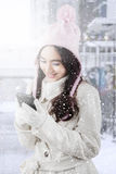 Girl in winter coat sending message with cellphone. Beautiful teenage girl wearing winter coat and smiling happy while sending message with cellphone in the city Royalty Free Stock Image