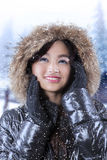 Girl with winter coat in snowy day. Beautiful teenage girl wearing winter jacket while standing on the street in snowy day Stock Photo