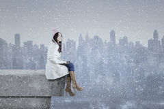 Girl in winter coat using laptop on the roof Stock Images