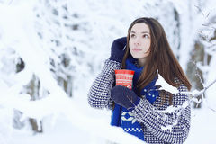 Girl at  winter forest with cup of hot drink Stock Photography