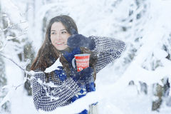 Girl at  winter forest with cup of hot drink Stock Photos
