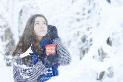Girl at  winter forest with cup of hot drink Stock Images