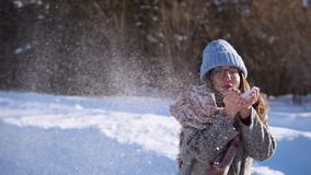 Girl in winter forest fun. Brunette blows snow from her hands. stock video footage